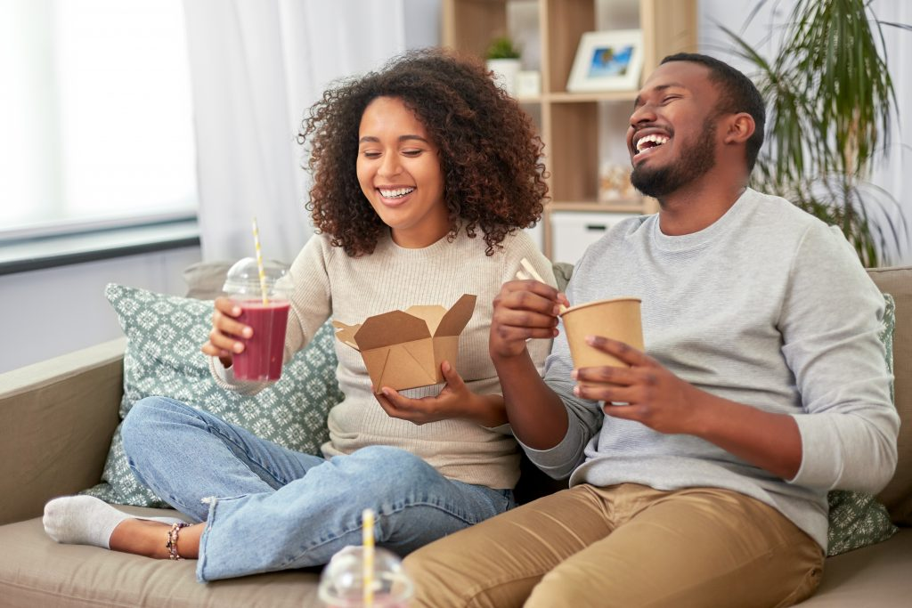 Happy Black couple enjoy takeout and drink a berry smoothie with a straw to help keep their teeth white.