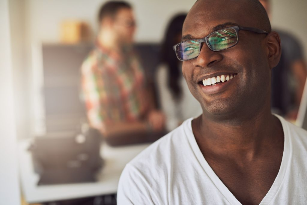 Handsome Black man in white T-shirt smiles with bright, white, straight teeth.
