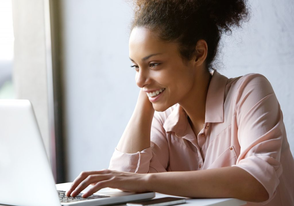 A beautiful black woman in pink shirt with her hair pulled back, searches for how to choose a dentist on her laptop.