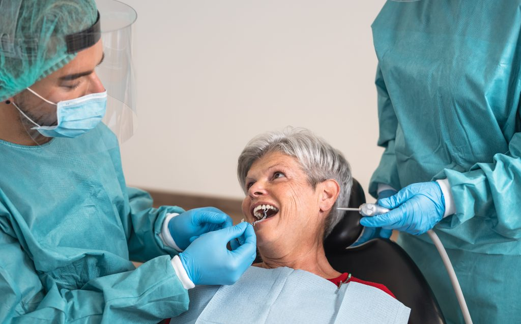 Two prosthodontists work with a mature woman to help replace missing teeth and restore her smile.