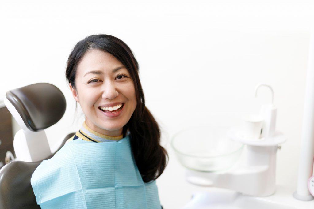 An Asian woman wearing blue dental blue bib smiles at the dental office.