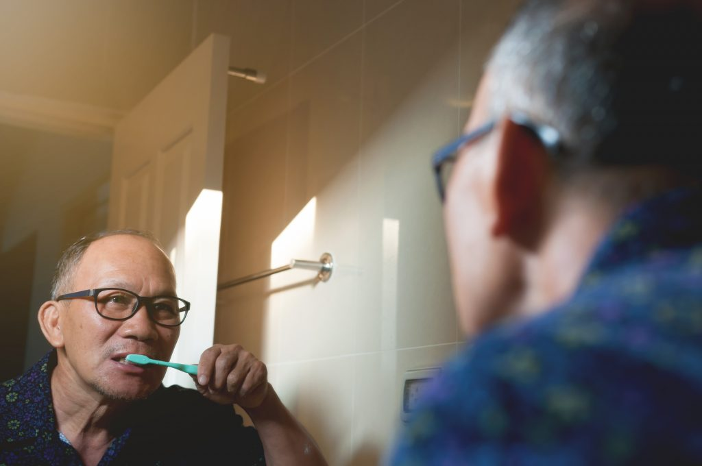 Mature Asian male wearing black glasses brushes his teeth with a blue-green toothbrush.