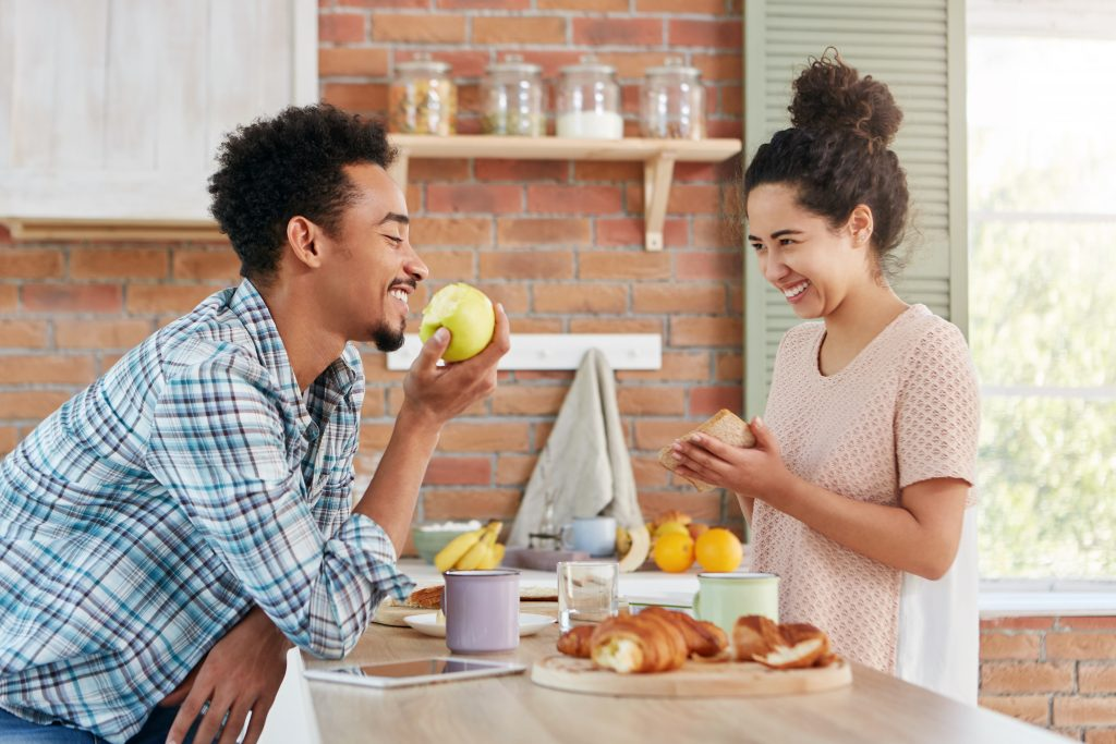 Black man smiles while eating an apple in a kitchen with his wife.