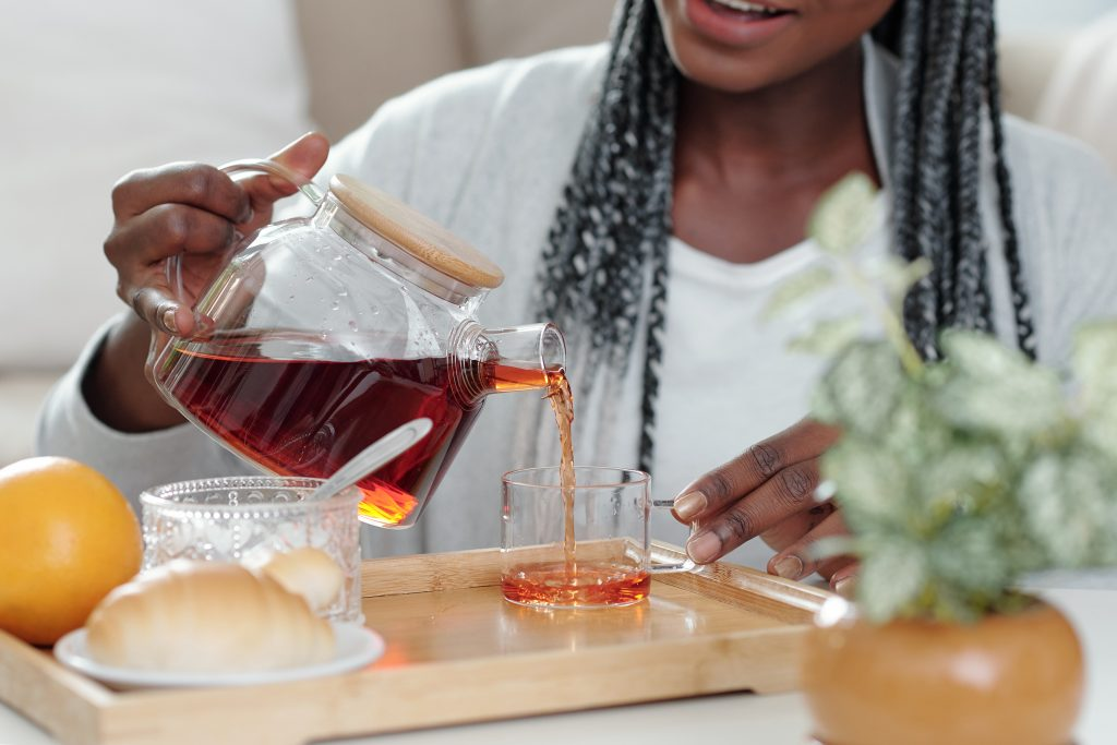 A Black woman pours herself a cup of hot tea at home .