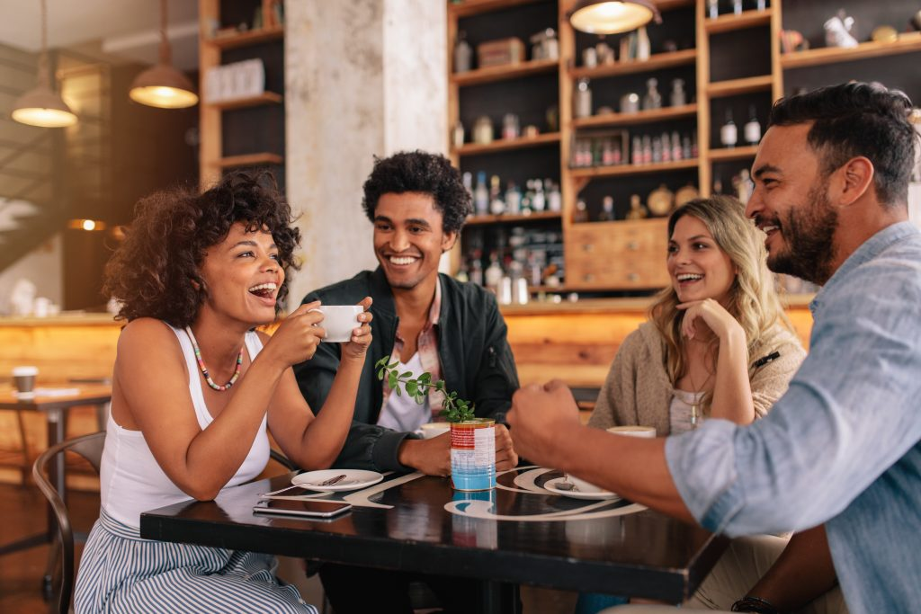 Group of multiracial friends enjoy coffee together at a local coffee shop.