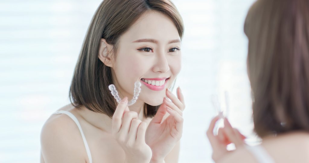 Young Asian woman smiles in the mirror while she holds a clear aligner used to straighten teeth.