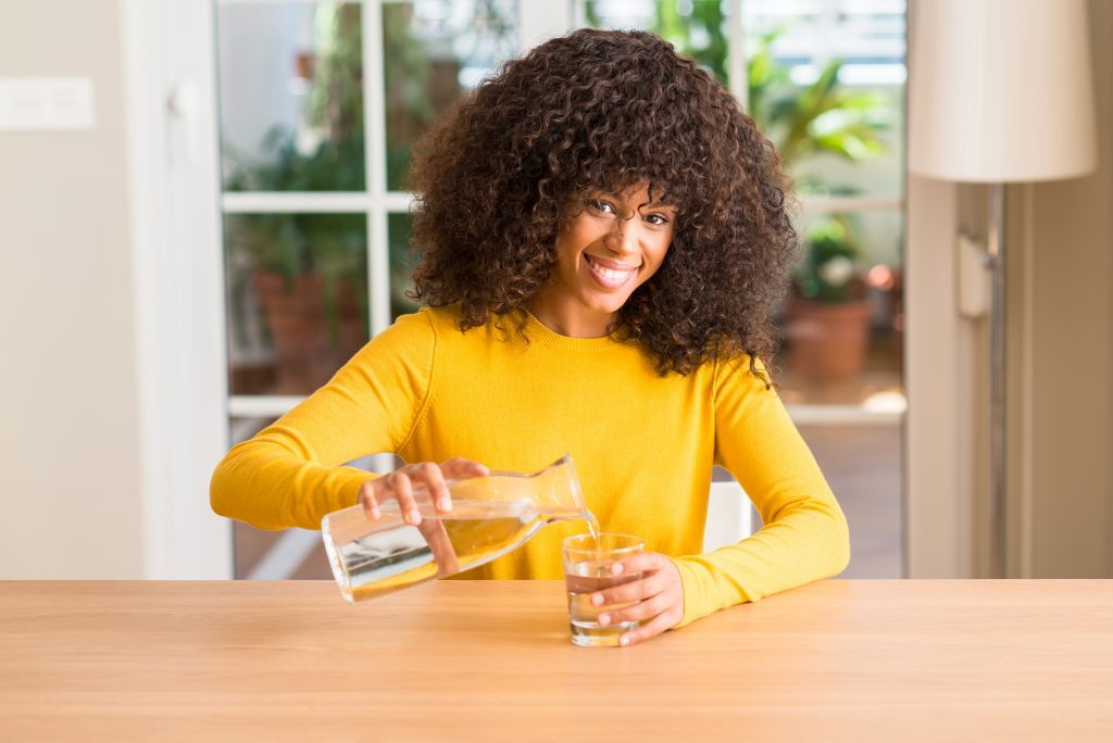 Attractive smiling Black woman pours a glass of water from a glass jar for a drink to help her dry mouth.