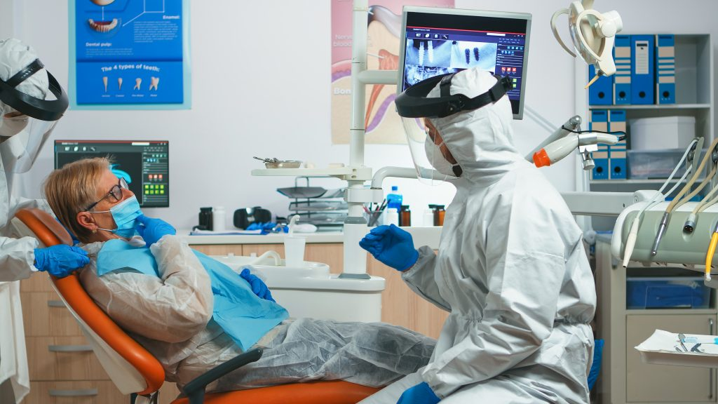 Dentists in full personal protective equipment (PPE) discuss dry mouth symptoms with an older female patient.