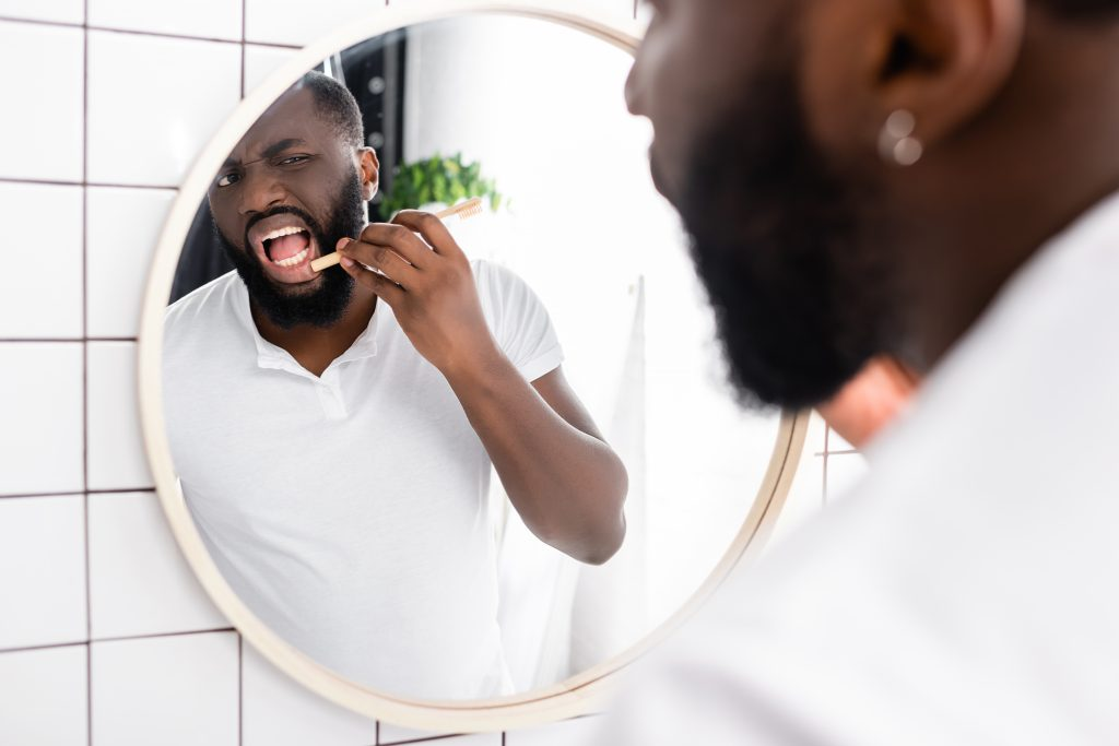 A Black man looks in the mirror and examines his gums for signs of periodontal disease.
