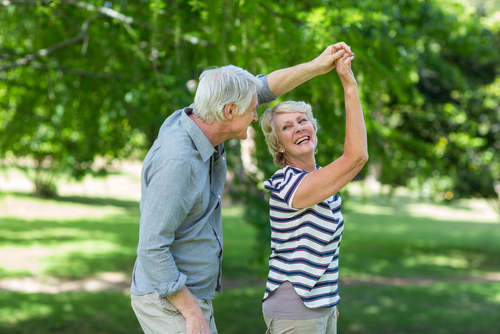 Senior man leads senior woman in a dance turn as they enjoy a day in the park together.