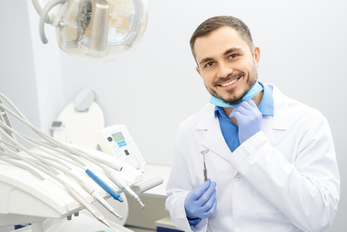 Professional dentist with a white coat smiles.