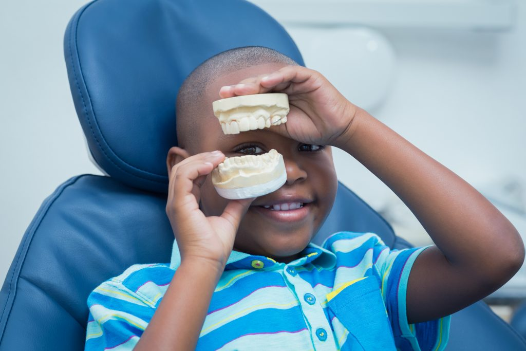 Young black male child wearing blue-striped shirt sitting in orthodontist chair holding a model of a mouth.