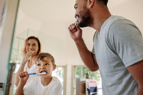 Boy brushes teeth, accompanied by his father and mother.