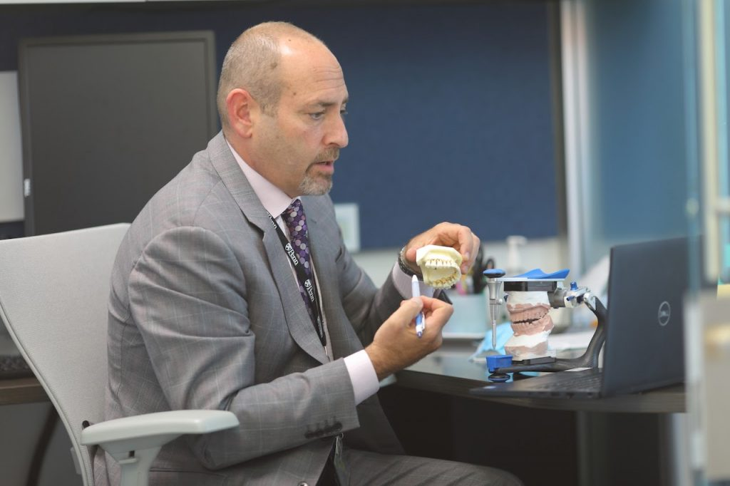 Assistant Dean for Intramural and Extramural Affairs, Dr. Todd Singer, pointing to a model of teeth with a pen.