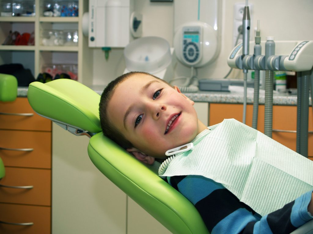 A young boy with short brown hair smiles as he waits in a dental chair for his pediatric dental visit to start.