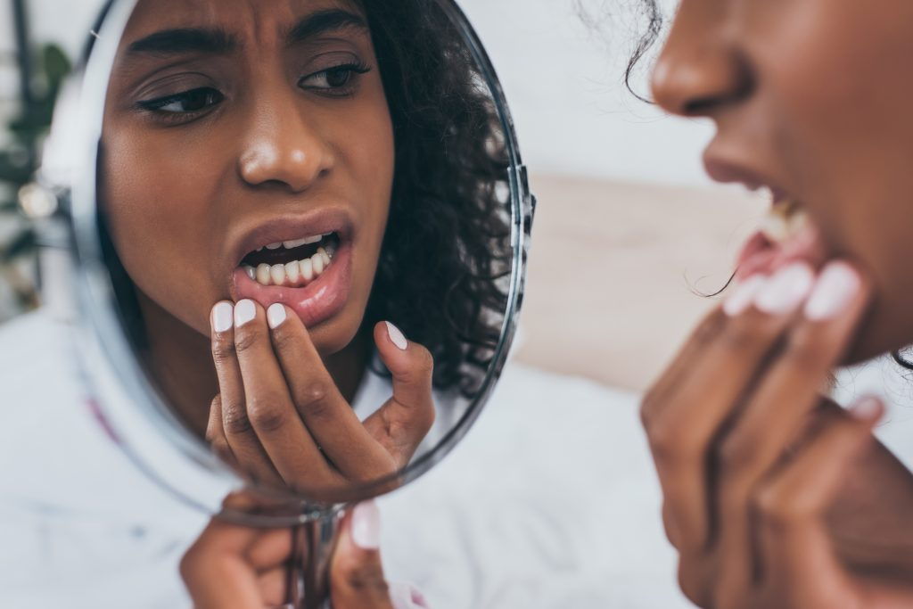 A young black woman examines her tooth enamel in a handheld mirror.