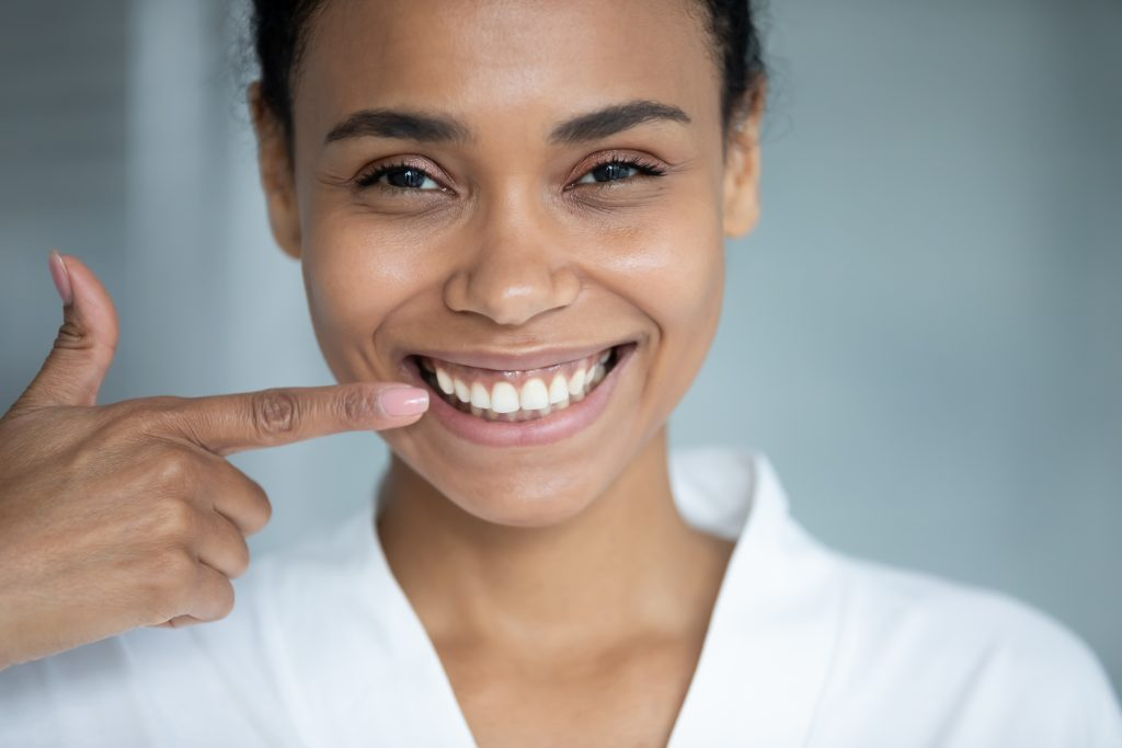 Black teen girl points to her healthy, bright smile after having her braces removed.