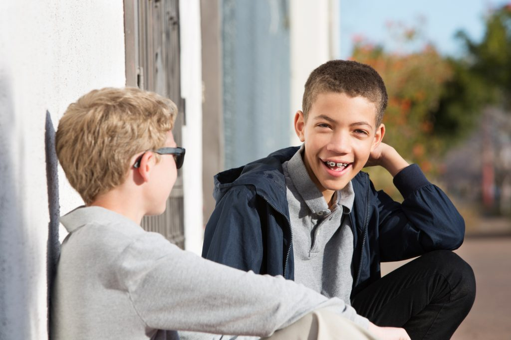 Young boy with braces on his teeth smiles while talking to a friend.