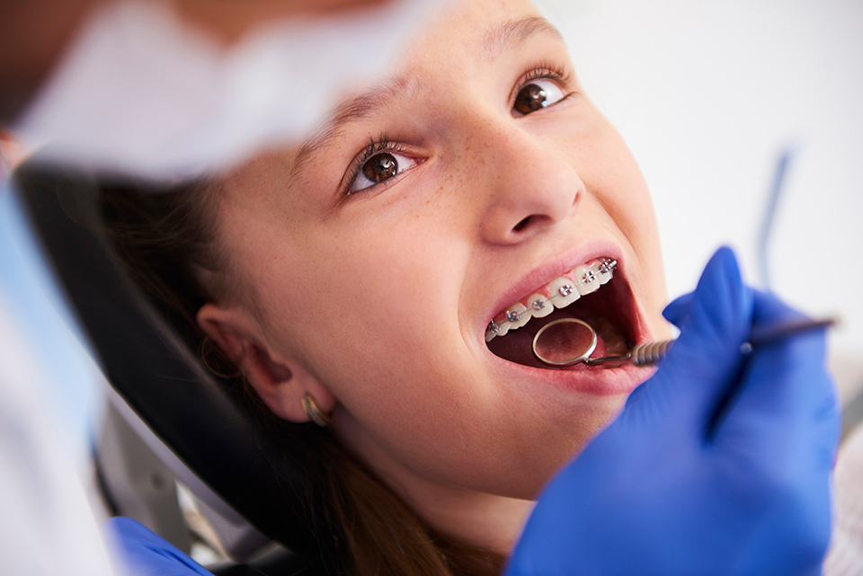 Young girl with braces looks up at the orthodontist during a dental exam.