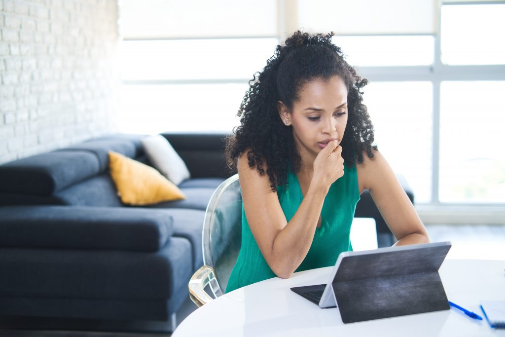 Nervous or stressed Black woman chews her fingernail while looking at a laptop computer.